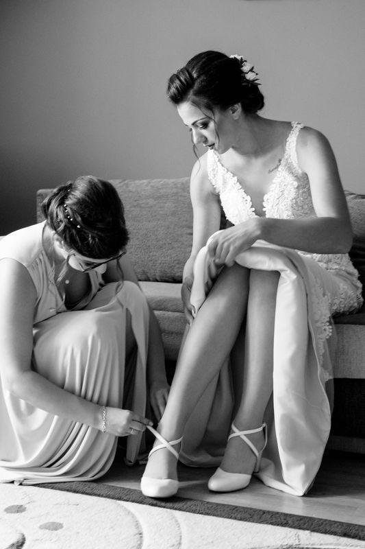 Druhna pomagająca zapiąć buty pannie młodej